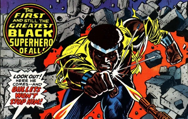 "Power Man punches through a brick wall facing gunfire, ""the first and still the greatest black superhero of all!"""